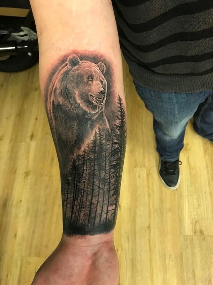 Ein schwarz Weiß Tattoo von einem Bären und dem Wald