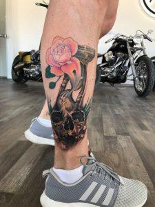 Tatto von einem Totenkopf mit einer Sanduhr auf dem Bein