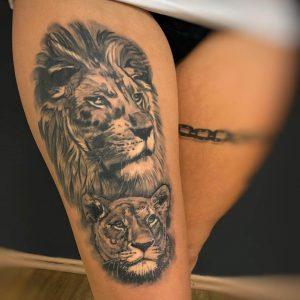 Tattoo von Zwei Löwen auf einem Frauenbein