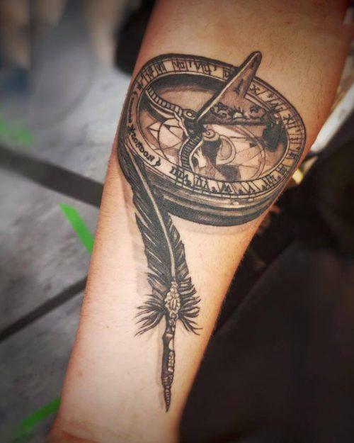 Tattoo von einer Feder und einem Kompass auf dem Arm Hamen Wild Spirit